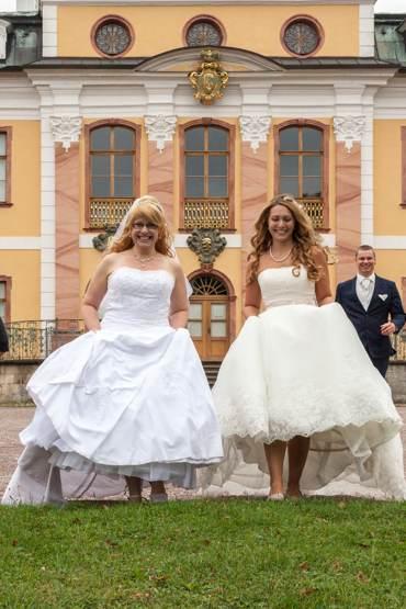 After Wedding Shooting mit Brautpaar im Park. Bräute raffen die Kleider und versuchen zu flüchten.