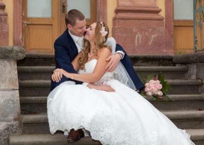 After Wedding Shooting mit Brautpaar im Park. Brautpaar schmust auf einer Treppe.
