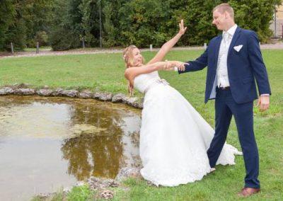 After Wedding Shooting mit Brautpaar im Park. Braut droht in einen Teich zu fallen, aber der Bräutigam hält Sie fest.