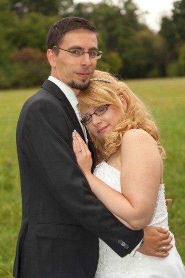 After Wedding Shooting mit Brautpaar im Park. Braut lehnt sich entspannt an Ihren Ehemann an.