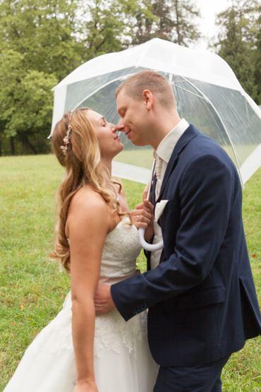 After Wedding Shooting mit Brautpaar im Park. Brautpaar läßt sich vom Regen nicht stören und küßt sich unterm Regenschirm.