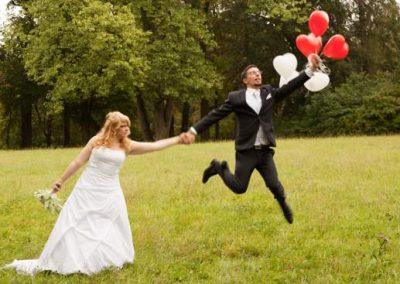 After Wedding Shooting mit Brautpaar im Park. Braut hält ihren Ehemann fest, der an Luftballons wegzufliegen droht.