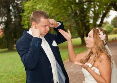 After Wedding Shooting mit Brautpaar im Park. Bräutigam will seiner Frau nicht zuhören und hält sich die Ohren zu.