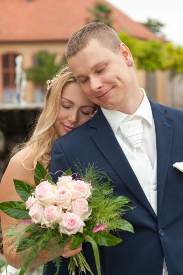 After Wedding Shooting mit Brautpaar im Park. Braut kuschelt sich an den Bräutigam an.