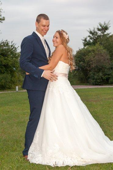 After Wedding Shooting mit Brautpaar im Park. Brautpaar steht auf einer Wiese und sieht äußerst glücklich aus.