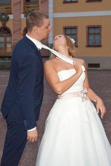 After Wedding Shooting mit Brautpaar im Park. Braut zieht den Bräutigam an der Krawatte zu sich.