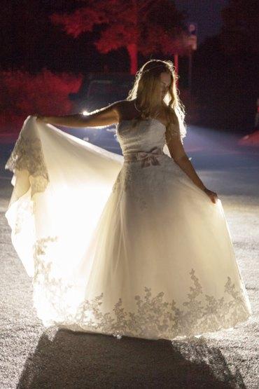 After Wedding Shooting mit Brautpaar im Park. Braut posiert im Scheinwerferlicht und zeigt ihr schönes Kleid.